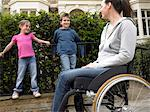 Mother in wheelchair in street with daughter and son (7-9) smiling Stock Photo - Premium Royalty-Free, Artist: Pierre Tremblay, Code: 6106-05452991