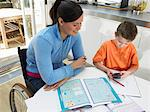 Mother in wheelchair at table helping son (7-9) with homework, smiling Stock Photo - Premium Royalty-Free, Artist: Pierre Tremblay, Code: 6106-05452997