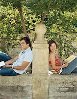 Couple sitting back to back against post on wall, holding books, smiling Stock Photo - Premium Royalty-Freenull, Code: 6106-05453051