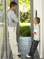 Father and son (7-9) facing each other in hallway Stock Photo - Premium Royalty-Freenull, Code: 6106-05454088