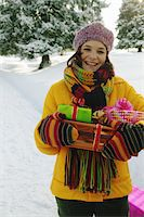 Mature woman holding presents in snow, smiling, portrait Stock Photo - Premium Royalty-Freenull, Code: 6106-05454668