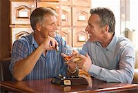 Two mature men drinking whiskey and smoking cigars at cigar bar Stock Photo - Premium Royalty-Freenull, Code: 6106-05455549
