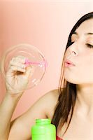 Teenage girl (16-18) blowing soap bubble Stock Photo - Premium Royalty-Freenull, Code: 6106-05455923