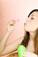 Teenage girl (16-18) blowing soap bubbles Stock Photo - Premium Royalty-Freenull, Code: 6106-05455924