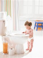 Male toddler (12-15 months) looking in toilet Stock Photo - Premium Royalty-Freenull, Code: 6106-05456289