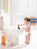 Male toddler (12-15 months) holding mobile phone over toilet Stock Photo - Premium Royalty-Freenull, Code: 6106-05456290