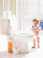 Male toddler (12-15 months) holding mobile phone in bathroom Stock Photo - Premium Royalty-Freenull, Code: 6106-05456291