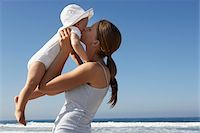 Mother kissing baby daughter up (4-6 months) on beach Stock Photo - Premium Royalty-Freenull, Code: 6106-05457735
