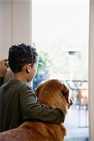 Boy (9-11) and dog looking out door, rear veiw Stock Photo - Premium Royalty-Freenull, Code: 6106-05458388