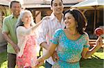 Family dancing conga in garden, young woman holding maraca, smiling Stock Photo - Premium Royalty-Freenull, Code: 6106-05460721
