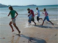 seniors woman in swimsuit - Family with two children (7-10) running on beach Stock Photo - Premium Royalty-Freenull, Code: 6106-05471402