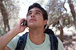 Young man wearing back sack on mobile phone outdoors, close-up Stock Photo - Premium Royalty-Freenull, Code: 6106-05474224