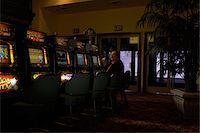 Senior man sitting at casino slot machine, smoking Stock Photo - Premium Royalty-Freenull, Code: 6106-05481566