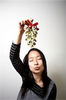 Young woman holding mistletoe, pursing lips, eyes closed Stock Photo - Premium Royalty-Freenull, Code: 6106-05484501
