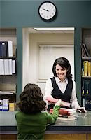 education loan - Girl (8-9) giving books to librarian in library Stock Photo - Premium Royalty-Freenull, Code: 6106-05485540