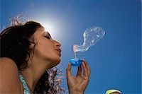 Young girl blowing bubbles Stock Photo - Premium Royalty-Freenull, Code: 6106-05490363