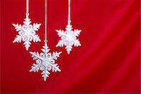 snowflakes  holiday - Silver snowflakes against a red silk backdrop.  Shallow depth of field/selective focus on front snowflake. Stock Photo - Premium Royalty-Freenull, Code: 6106-05490863