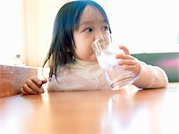 Girl who drinks water at a restaurant Stock Photo - Premium Royalty-Freenull, Code: 6106-05499995