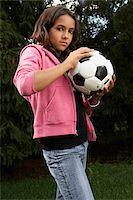Girl (12-13) standing in yard holding football, portrait Stock Photo - Premium Royalty-Freenull, Code: 6106-05502811