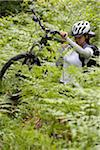 Mid adult woman walking amongst ferns carrying bike Stock Photo - Premium Royalty-Free, Artist: Aurora Photos, Code: 6106-05504146
