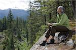 mature woman sitting at edge of rock, looking at view, smiling