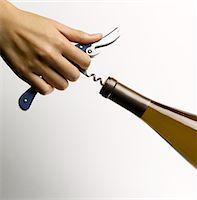 Female hand pulling cork from wine bottle Stock Photo - Premium Royalty-Freenull, Code: 6106-05506134