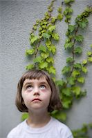 Girl (3-4) standing in front of wall with ivy, looking up (differential focus) Stock Photo - Premium Royalty-Freenull, Code: 6106-05506467