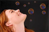 Young woman looking at soap bubbles, studio shot Stock Photo - Premium Royalty-Freenull, Code: 6106-05508715