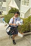 Postman walking past houses with pile of letters Stock Photo - Premium Royalty-Free, Artist: Michael Mahovlich, Code: 6106-05509144