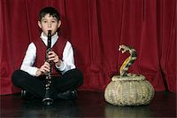 Boy (8-9) playing clarinet on stage charming snake Stock Photo - Premium Royalty-Freenull, Code: 6106-05509613
