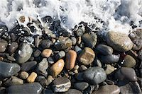 Surf splashes over stones on beach Stock Photo - Premium Royalty-Freenull, Code: 6106-05510771