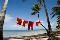 Santa Claus costume hanging on clothesline on tropical beach Stock Photo - Premium Royalty-Freenull, Code: 6106-05511016