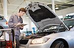 Mechanic examining car engine in garage Stock Photo - Premium Royalty-Free, Artist: Blend Images, Code: 649-05521239