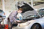Mechanic examining car engine in garage Stock Photo - Premium Royalty-Free, Artist: Blend Images, Code: 649-05521240