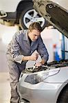 Mechanic working on car engine in garage Stock Photo - Premium Royalty-Free, Artist: Blend Images, Code: 649-05521249