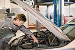 Mechanic working on car engine in garage Stock Photo - Premium Royalty-Free, Artist: Blend Images, Code: 649-05521251