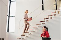 Businesswoman climbing stairs in office Stock Photo - Premium Royalty-Freenull, Code: 649-05521387