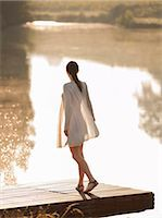 Woman standing on dock of lake Stock Photo - Premium Royalty-Freenull, Code: 649-05522359