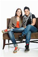 Lesbian couple on sofa against white background Stock Photo - Premium Royalty-Freenull, Code: 614-05523008