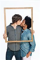 Gay couple kissing with picture frame against white background Stock Photo - Premium Royalty-Freenull, Code: 614-05523028