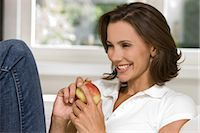 Smiling woman holding an apple Stock Photo - Premium Rights-Managednull, Code: 853-05523412