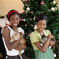 preteen girl pussy - Two sisters (11-13) holding kittens in front of Christmas tree Stock Photo - Premium Royalty-Freenull, Code: 6106-05525144