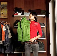Young woman holding vest on hanger in clothing store Stock Photo - Premium Royalty-Freenull, Code: 6106-05525857