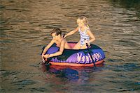 Girl (6-9) and boy (8-9) in inflatable ring in sea Stock Photo - Premium Royalty-Freenull, Code: 6106-05528411