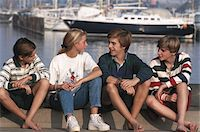 Friends (12-17) sitting by harbour, smiling Stock Photo - Premium Royalty-Freenull, Code: 6106-05528759