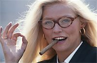 Woman with cigar in mouth, smiling, portrait Stock Photo - Premium Royalty-Freenull, Code: 6106-05528904