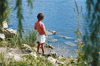 Boy (4-5) urinating by river, rear view Stock Photo - Premium Royalty-Freenull, Code: 6106-05529712