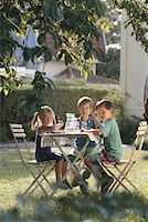 Children (6-9) sitting at table in lawn Stock Photo - Premium Royalty-Freenull, Code: 6106-05529973