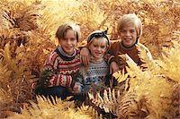 Children (6-9) sitting between trees, smiling, portrait Stock Photo - Premium Royalty-Freenull, Code: 6106-05530029