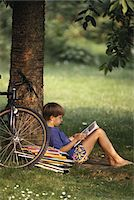 Boy (10-11) leaning against tree, reading book, side view Stock Photo - Premium Royalty-Freenull, Code: 6106-05530190